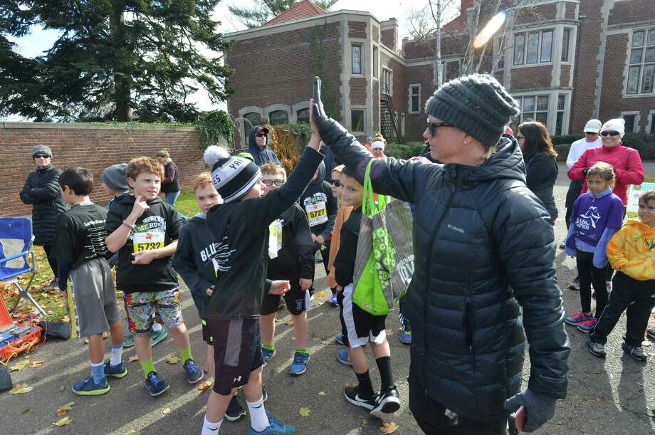 "Kristina Gregory high fives the members of ""Let me Run"" team from The Royle Elementary School in Darien at the New Canaan Turkey Trot on Sunday, November. 19 2017 in New Canaan Conn. The 14th annual 5K run/walk at Waveny Park donates its proceeds from the race to benefit The Open Door Shelter and its programs in Norwalk Conn. The shelter provides supportive housing and emergency shelter to those in need in the area, and their kitchen and food pantry provide over 30,000 meals every month to people struggling to make ends meet. Photo: Alex Von Kleydorff / Hearst Connecticut Media / Norwalk Hour"