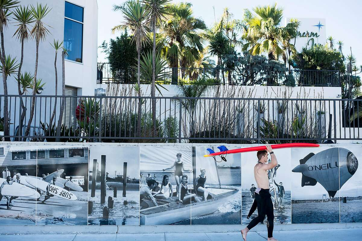 A surfer passes a mural of Jack O'Neill imagery outside the Dream Inn on Nov. 18, 2017 in Santa Cruz.