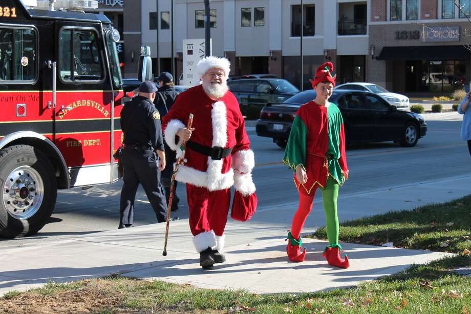 Santa Claus and one of his elves walk from a fire truck to his temporary home in Edwardsville City Park on Saturday. Santa will be available to meet with children from 5:30 p.m. to 8:30 p.m. on Wednesdays and 1 p.m. to 4 p.m. on Saturdays through Dec. 20. Parents may bring their own cameras to take photographs. Photo: Bill Tucker