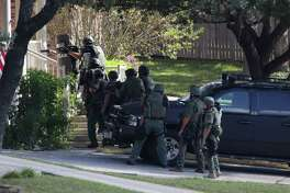 SWAT team moves to the front door of the house at 13827 Possum Tree where two shots were fired, on Monday , Nov.27, 2017.