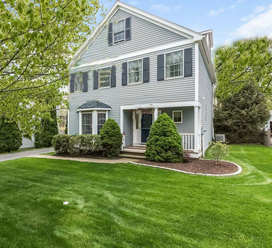 The colonial house at 19 Bailey Avenue is actually beige with burgundy shutters but the homeowners and listing agent have provided photos to show how it would look painted gray since that is a popular color for many potential home-buyers.