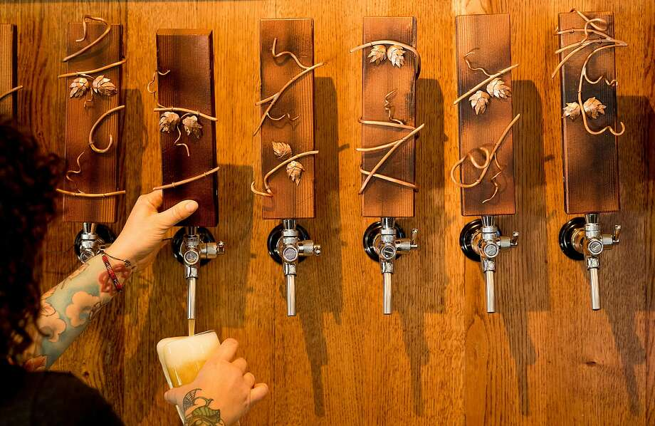Bartender Grace Guerra pours a beer at Sante Adairius' Santa Cruz Portal, in Santa Cruz, Calif. Local woodmaker Chris Blanchard made the tap handles custom for the taproom. Photo: Noah Berger / Special To The Chronicle