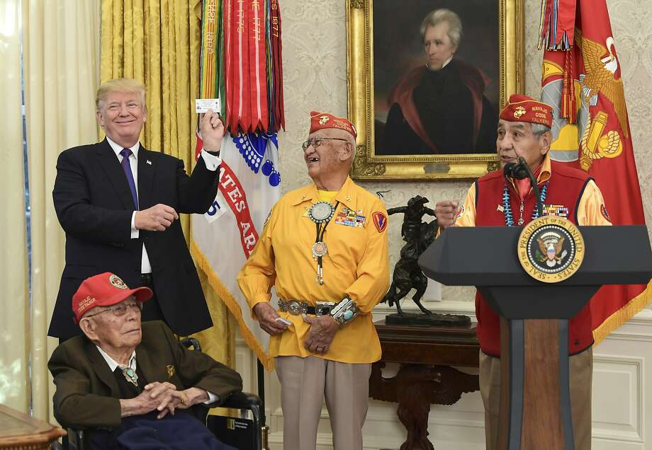 President Donald Trump, standing left, holds up the card of Navajo Code Talker Thomas Begay, center, during their meeting in the Oval Office of the White House in Washington, Monday, Nov. 27, 2017. Photo: Susan Walsh, Associated Press