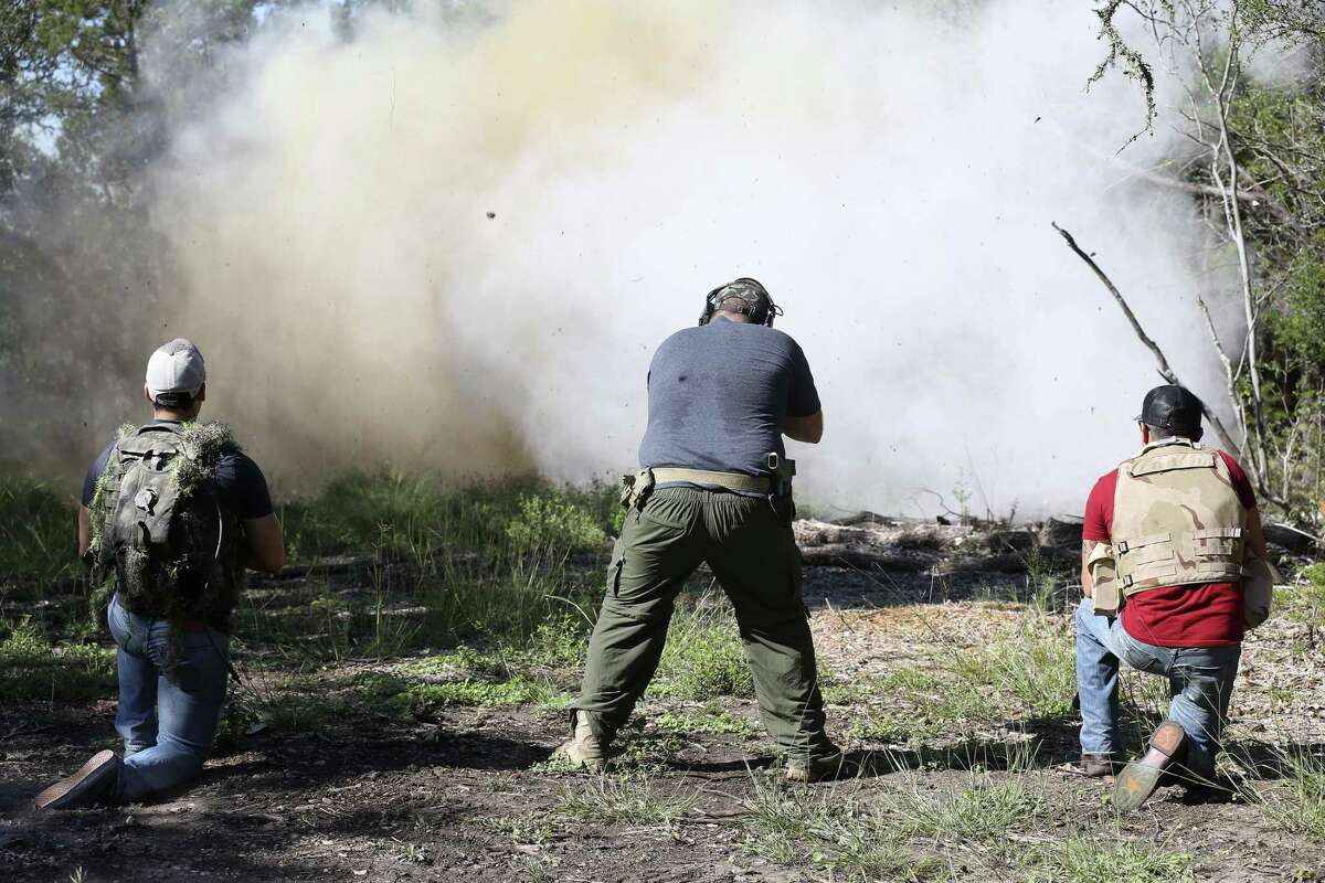 Hispanic veterans Justin Bernal, 26, right, and Anthony Cumpian, 24, left, watch as Viking Endeavor's Jeramy Rumley, 38, blows up a bag of Tannerite in Mico, Texas.