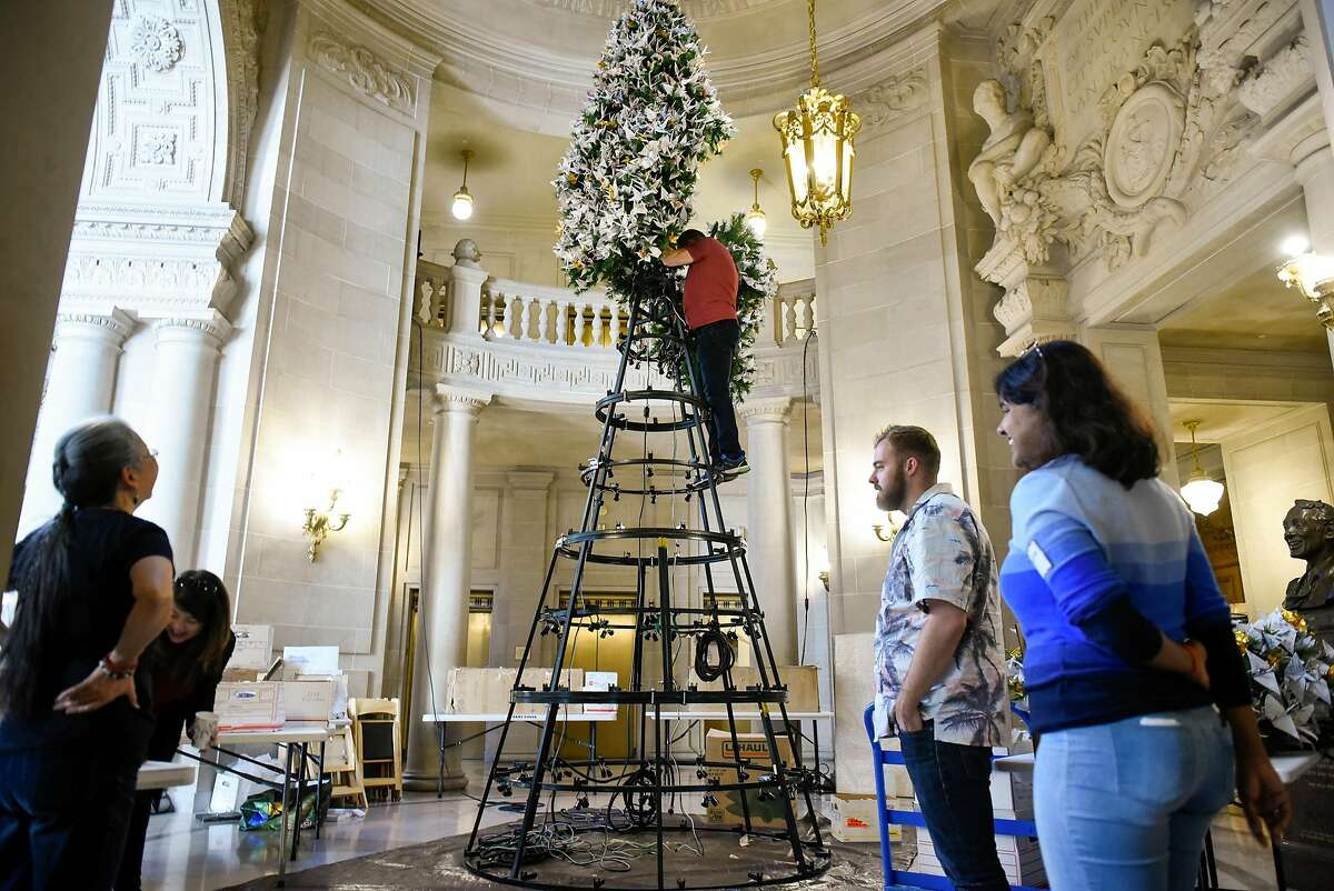 """Volunteers watch as Jeff Cotter, of the Rainbow World Fund, attaches a branch to the top of the Rainbow World Fund """"World Tree of Hope"""" at City Hall in San Francisco, CA, on Monday November 27, 2017."""