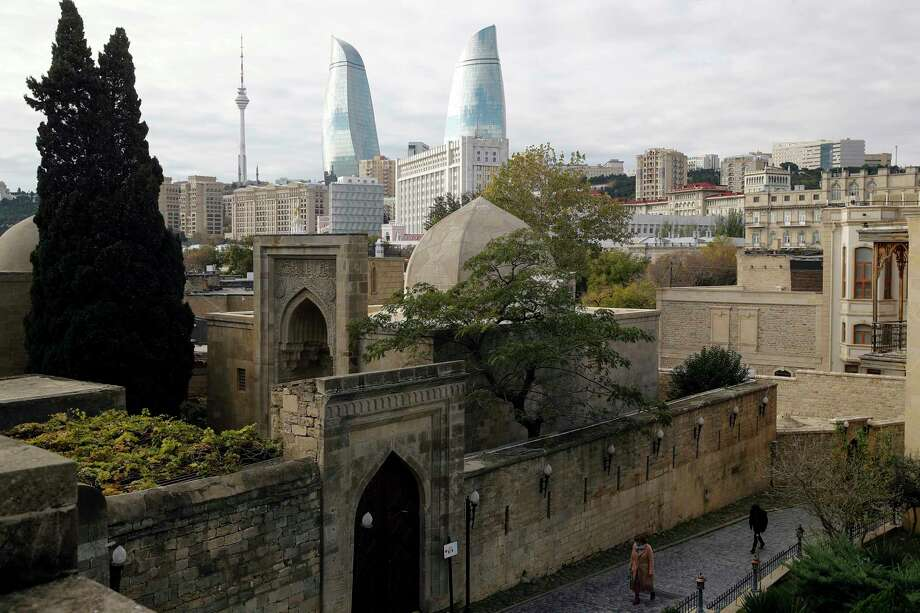 People walk in the Old City of Baku with the Flame Towers skyscrapers in background in Baku, Azerbaijan, on Nov. 23, 2017. (AP Photo/Pavel Golovkin) Photo: Pavel Golovkin, STF / Copyright 2017 The Associated Press. All rights reserved.