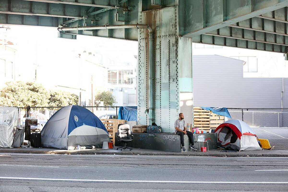 A man sits outside near his tent at a tent encampment on Bryant Street on October 15, 2017 in San Francisco, Calif.