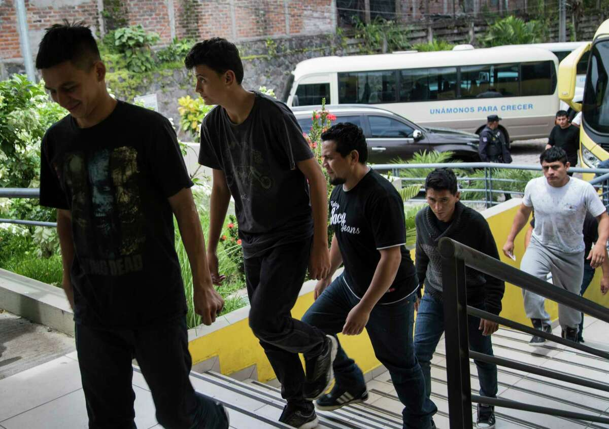 Salvadorian deportees walk away from busses toward the Centro de Atención Integral para Migrantes, Thursday, Sept. 28, 2017, in San Salvador. At the center they are provided orientation, fresh clothing, and the opportunity to call their family members so they can be picked up. The center is located in the colony Quiñonez in San Salvador, also known as the