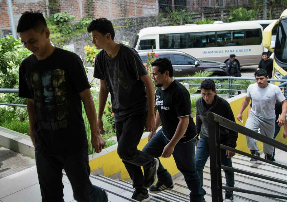 "Salvadorian deportees walk away from busses toward the Centro de Atención Integral para Migrantes, Thursday, Sept. 28, 2017, in San Salvador. At the center they are provided orientation, fresh clothing, and the opportunity to call their family members so they can be picked up. The center is located in the colony Quiñonez in San Salvador, also known as the ""La Chacra."" Photo: Marie D. De Jesus, Houston Chronicle / © 2017 Houston Chronicle"