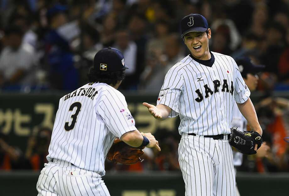 Starting pitcher Shohei Otani (R) #16 of Japan high fives with infielder Nobuhiro Matsuda (L) #3 after the top of sixth inning during the WBSC Premier 12 semi final match between South Korea and Japan at the Tokyo Dome on November 19, 2015 in Tokyo, Japan.  (Photo by Masterpress/Getty Images) Photo: Masterpress, Getty Images