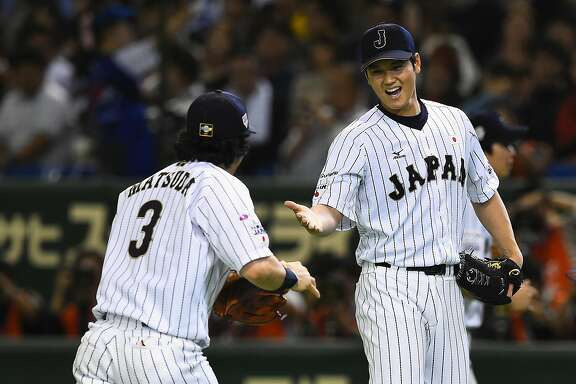 TOKYO, JAPAN - NOVEMBER 19:  Starting pitcher Shohei Otani (R) #16 of Japan high fives with infielder Nobuhiro Matsuda (L) #3 after the top of sixth inning during the WBSC Premier 12 semi final match between South Korea and Japan at the Tokyo Dome on November 19, 2015 in Tokyo, Japan.  (Photo by Masterpress/Getty Images)