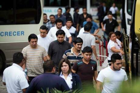 Salvadoran deportees walk away from buses toward the government's migrant assistance center in San Salvador, where they are provided help with orientation, fresh clothing, and the opportunity to call their families to pick them up.