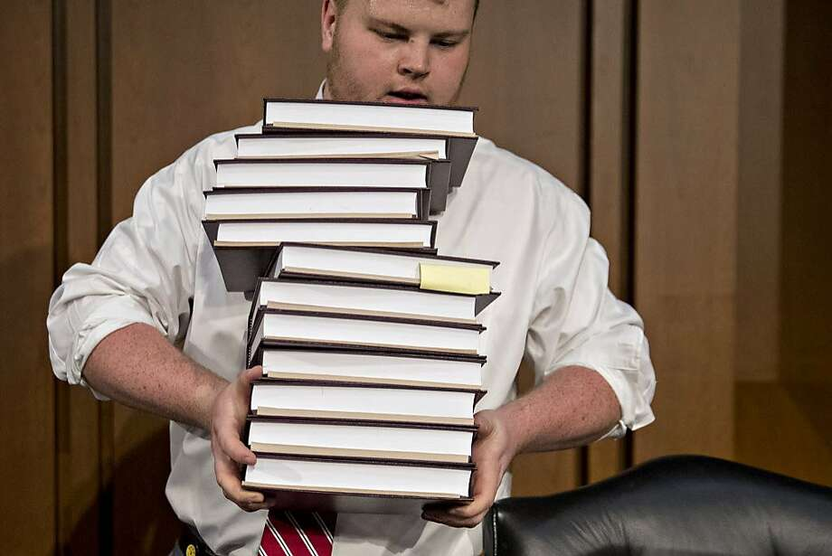 An aide carrying tax code books before a Senate committee hearing on tax cut legislation this month. Photo: Andrew Harrer, Bloomberg