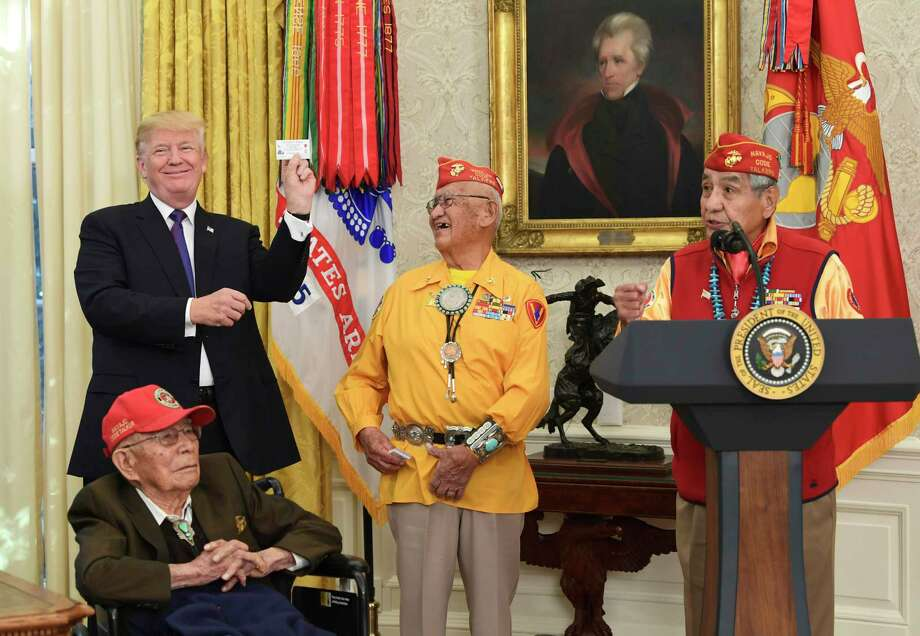 President Donald Trump holds up the card of Navajo Code Talker Thomas Begay, center, during their meeting in the Oval Office on Monday. Photo: Susan Walsh, STF / Copyright 2017 The Associated Press. All rights reserved.
