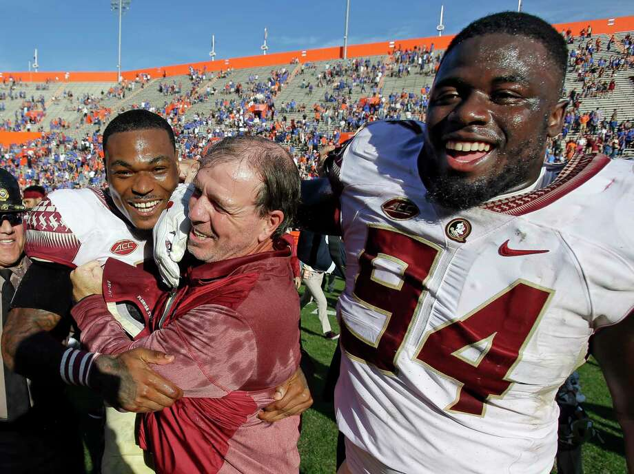 Florida State defensive back Derwin James, left, and defensive tackle Walvenski Aime (94) celebrate with Florida State head coach Jimbo Fisher, center, after defeating Florida 38-22 in an NCAA college football game, Saturday, Nov. 25, 2017, in Gainesville, Fla. Florida State won 38-22. (AP Photo/John Raoux) Photo: John Raoux, STF / Copyright 2017 The Associated Press. All rights reserved.