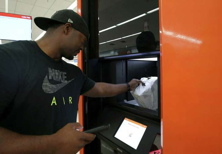 Tracy Porch retrieves three wireless headphones he ordered online on Black Friday at the Walmart Online Pickup Tower Monday, Nov. 27, 2017, in Katy, Texas. ( Godofredo A. Vasquez / Houston Chronicle )