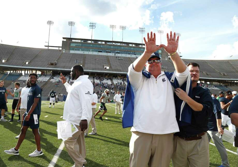 Rice football coach David Bailiff participates in a ritual during the playing of the school song as a fan drapes a Rice flag over his shoulders after the 30-14 loss to North Texas on Saturday at Rice Stadium. It was Bailiff's last game as Rice coach. Photo: Karen Warren, Staff / © 2017 Houston Chronicle