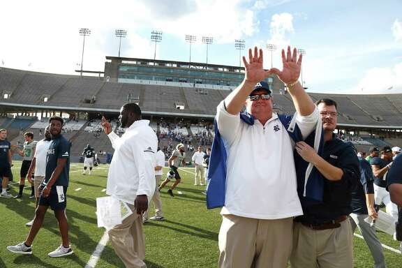 Rice football coach David Bailiff participates in a ritual during the playing of the school song as a fan drapes a Rice flag over his shoulders after the 30-14 loss to North Texas on Saturday at Rice Stadium. It was Bailiff's last game as Rice coach.