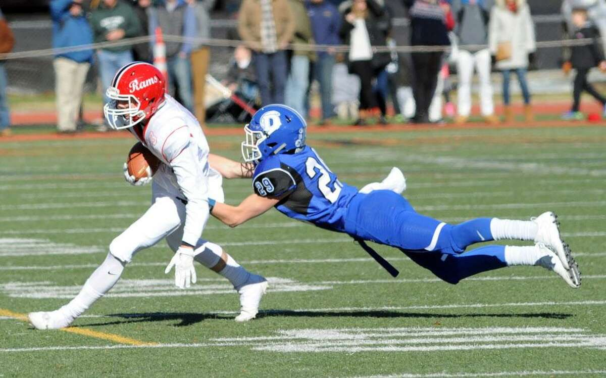 New Canaan receiver Sean Knight, left, runs the ball after making a catch as Darien defender Tyler Herget attempts the diving tackle during the 2017 Turkey Bowl high school football game between Darien High School and New Canaan High School at Boyle Stadium in Stamford, Conn., Thursday, Nov. 23, 2017. New Canaan won the game 27-0, beating an undefeated Darien team that was without starting quarterback Jack Joyce and star defensive back Brian Minicus, both of whom were arrested Wednesday night on charges stemming from an assault earlier in the month.