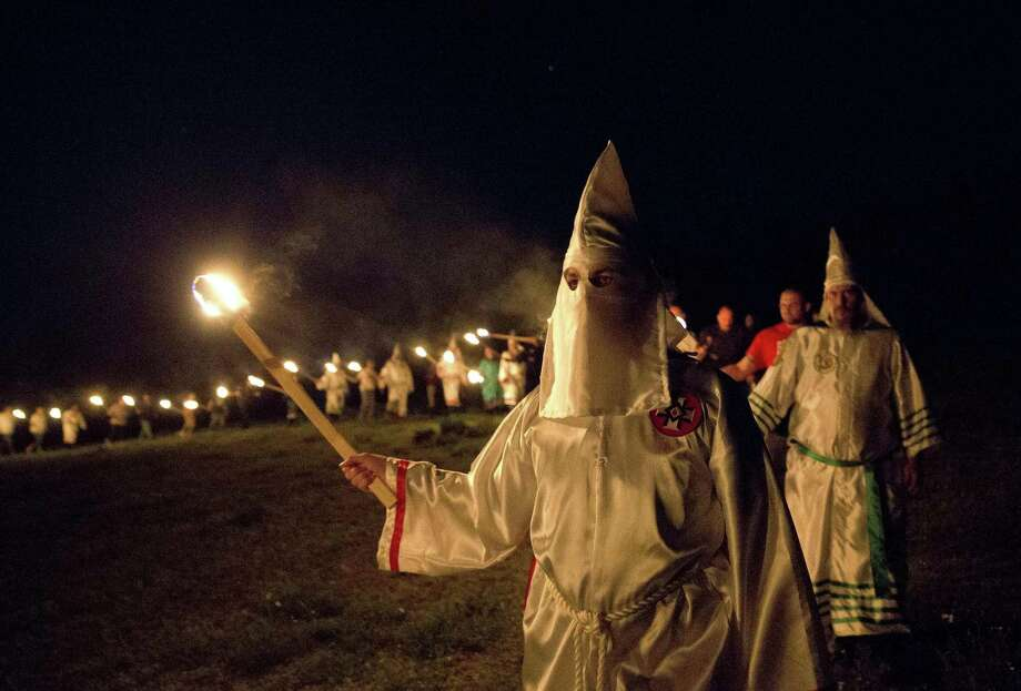 "In this Saturday, April 23, 2016, photo, members of the Ku Klux Klan participate in cross burnings after a ""white pride"" rally in rural Paulding County near Cedar Town, Ga. Born in the ashes of the smoldering South after the Civil War, the KKK died and was reborn before losing the fight against civil rights in the 1960s. Membership dwindled, a unified group fractured, and one-time members went to prison for a string of murderous attacks against blacks. Many assumed the group was dead, a white-robed ghost of hate and violence. Photo: Associated Press File Photo / Copyright 2016 The Associated Press. All rights reserved. This material may not be published, broadcast, rewritten or redistribu"