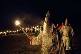 "In this Saturday, April 23, 2016, photo, members of the Ku Klux Klan participate in cross burnings after a ""white pride"" rally in rural Paulding County near Cedar Town, Ga. Born in the ashes of the smoldering South after the Civil War, the KKK died and was reborn before losing the fight against civil rights in the 1960s. Membership dwindled, a unified group fractured, and one-time members went to prison for a string of murderous attacks against blacks. Many assumed the group was dead, a white-robed ghost of hate and violence."