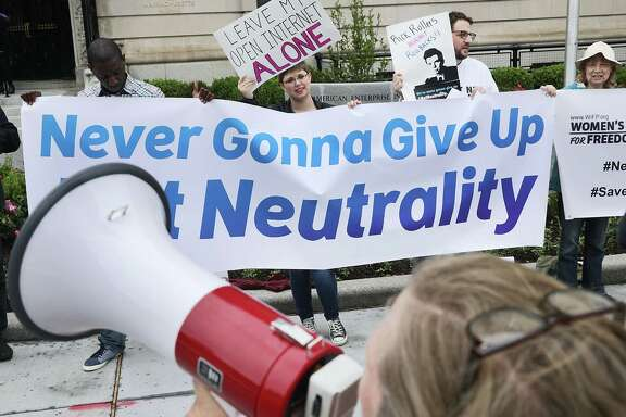 Proponents of net neutrality protest in May against Federal Communication Commission Chairman Ajit Pai in Washington.