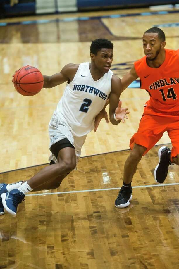 Northwood sophomore Trey McBride dribbles toward the basket as Findlay senior Martyce Kimbrough guards him during their game on Monday at Northwood University. (Katy Kildee/kkildee@mdn.net)