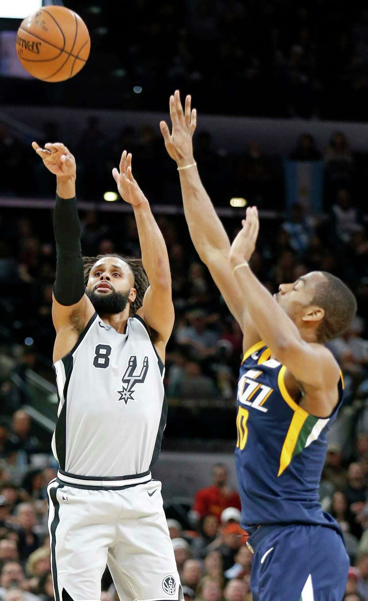 San Antonio Spurs' Patty Mills shoots around Utah Jazz's Alec Burks during first half action Saturday Feb. 3, 2018 at the AT&T Center.