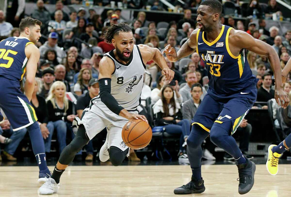 San Antonio Spurs' Patty Mills drives between Utah Jazz's Raul Neto (left) and Utah Jazz's Ekpe Udoh during first half action Saturday Feb. 3, 2018 at the AT&T Center.