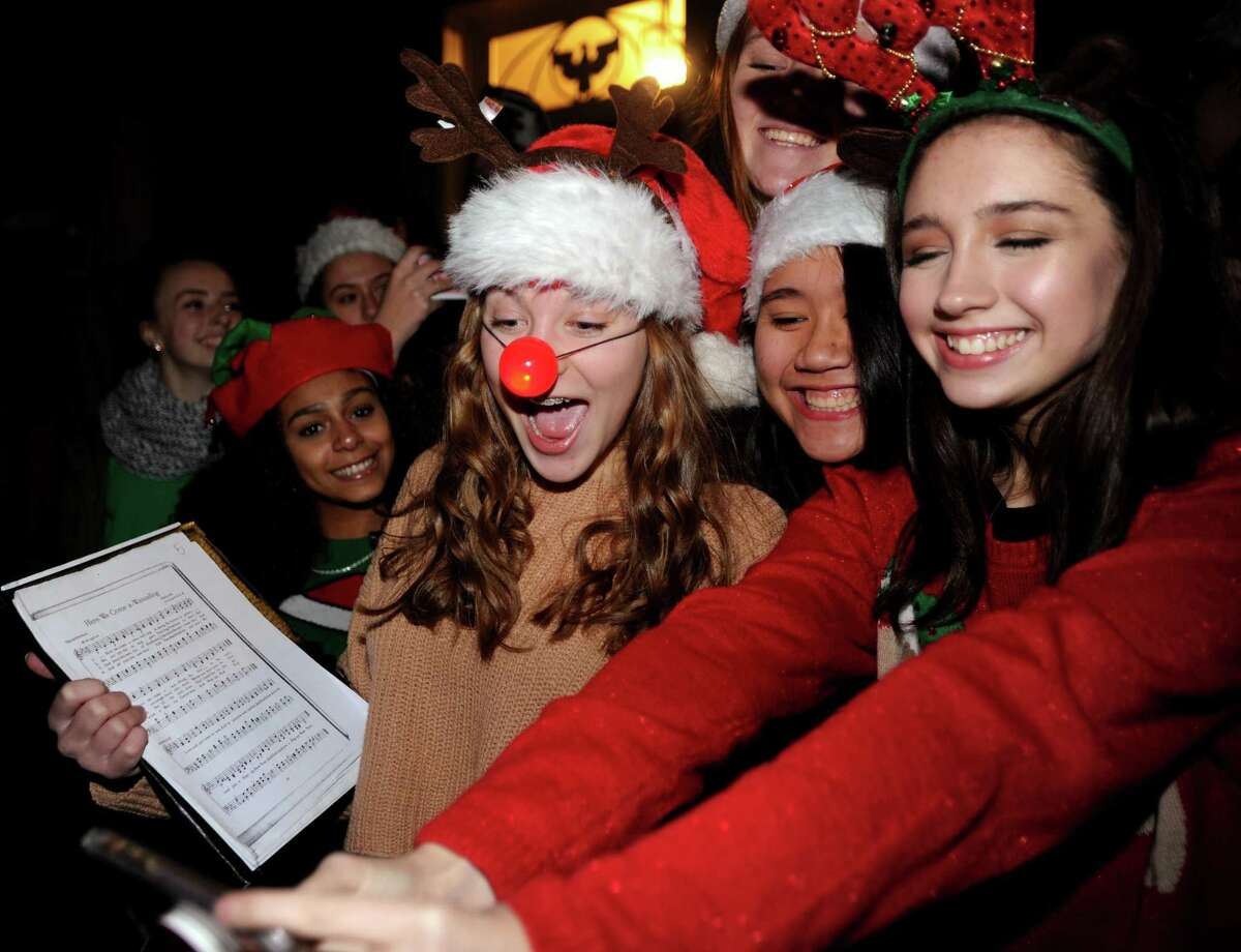 Alexis Detuzzi, center, Madeline Swanson, right, both 14, and other members of the Stratford High School choir pose for a selfie before performing carols at the Town of Stratford's Holiday Lighting Festival at Town Hall in Stratford, Conn. on Monday, November 27, 2017.
