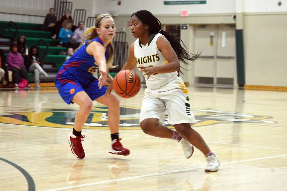 MELHS guard Destiny Williams, right, drives past a Roxana defender during third-quarter action inside Thomas Hooks Gym on Monday in Edwardsville.