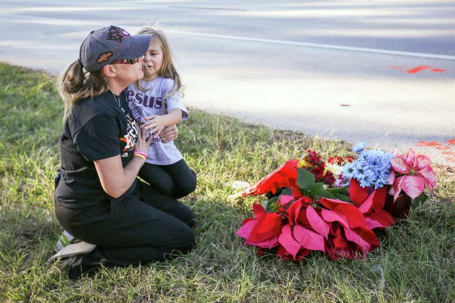 Ashley Axelson consoles her daughter Riley, 4, on Monday after she left flowers at an impromptu memorial for ASI Gymnastics coach Mike DeLuke off of FM 1488. Riley was one of DeLuke's more than 130 students at The Woodlands-based gymnasium. Photo: Michael Minasi, Staff Photographer / © 2017 Houston Chronicle