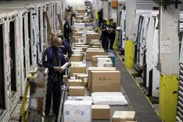 Employees sort packages for delivery on Monday at a FedEx shipping center in Chicago amid growth in online shopping.
