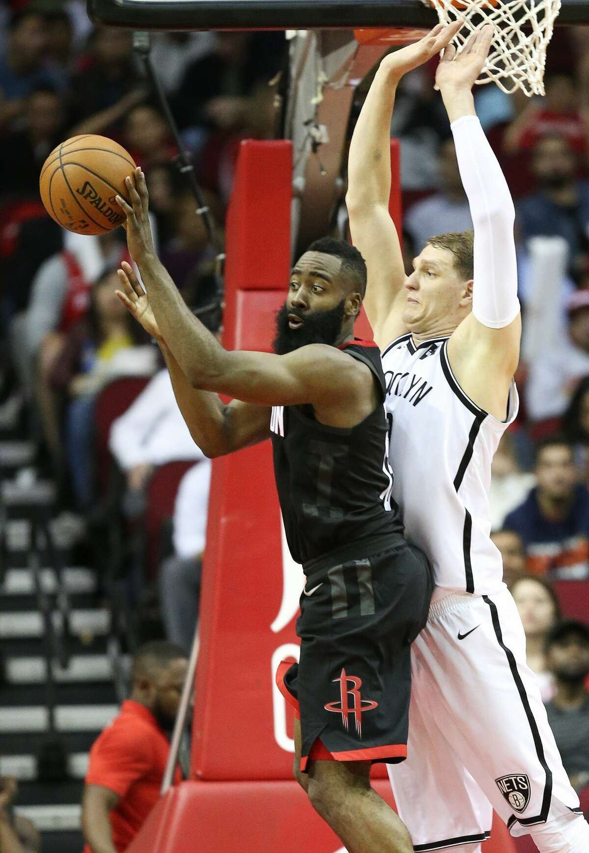 Houston Rockets guard James Harden, left, passes the ball as Brooklyn Nets center Timofey Mozgov defends during the second half of an NBA basketball game, Monday, Nov. 27, 2017, in Houston. Houston won the game 117-103. (AP Photo/Eric Christian Smith)