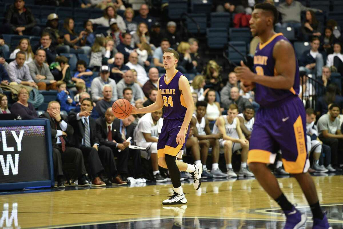 UAlbany's Joe Cremo carries the ball against Monmouth University in West Long Branch, N.J., on Monday, November 27, 2017. Teammate Travis Charles is on the right. (Karlee Sell / Monmouth University)