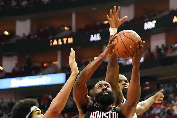 Rockets guard James Harden (13) splits the gap between Nets center Jarrett Allen, left, and guard Isaiah Whitehead on his way to 37 points.