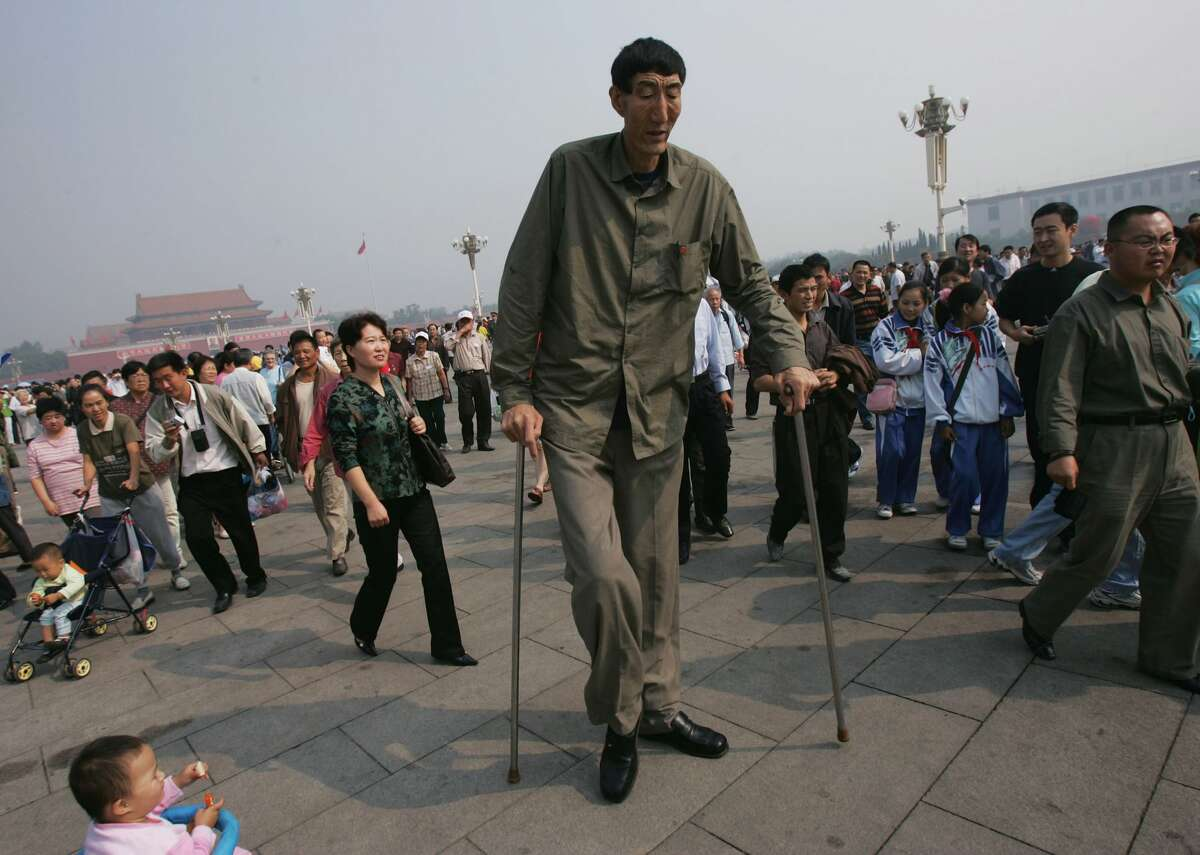 Bao Xishun, a Chinese man who measures 2.361 meters (about 7 feet 8 inches) walks during a sightseeing event at the Tiananmen Square September 27, 2005 in Beijing, China. 55-year-old Bao, a herdsman from Inner Mongolia Autonomous Region, was officially declared as the world's tallest naturally-growing human during a ceremony by the headquarters of Guinness World Records in London on September 22.