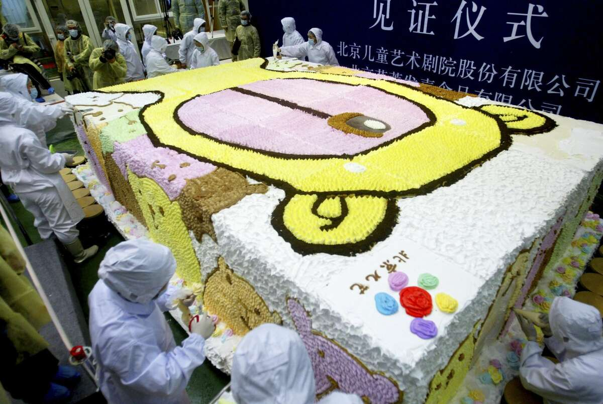 Chinese workers make the last adjustments to a cake during an attempt to break the Guinness World Record for the biggest ice-cream cake at Baxy ice-cream factory on January 16, 2006 in Beijing, China. The Guinness World Records' Chinese liaison officer announced that the ice-cream cake in this photo which is 4.8 meters (15.7 feet) long, three meters (9.8 feet) wide, one meter (3.3 feet) high and weighs eight tons (7,257 kg), is the new Guinness World Record for the biggest ice-cream cake.