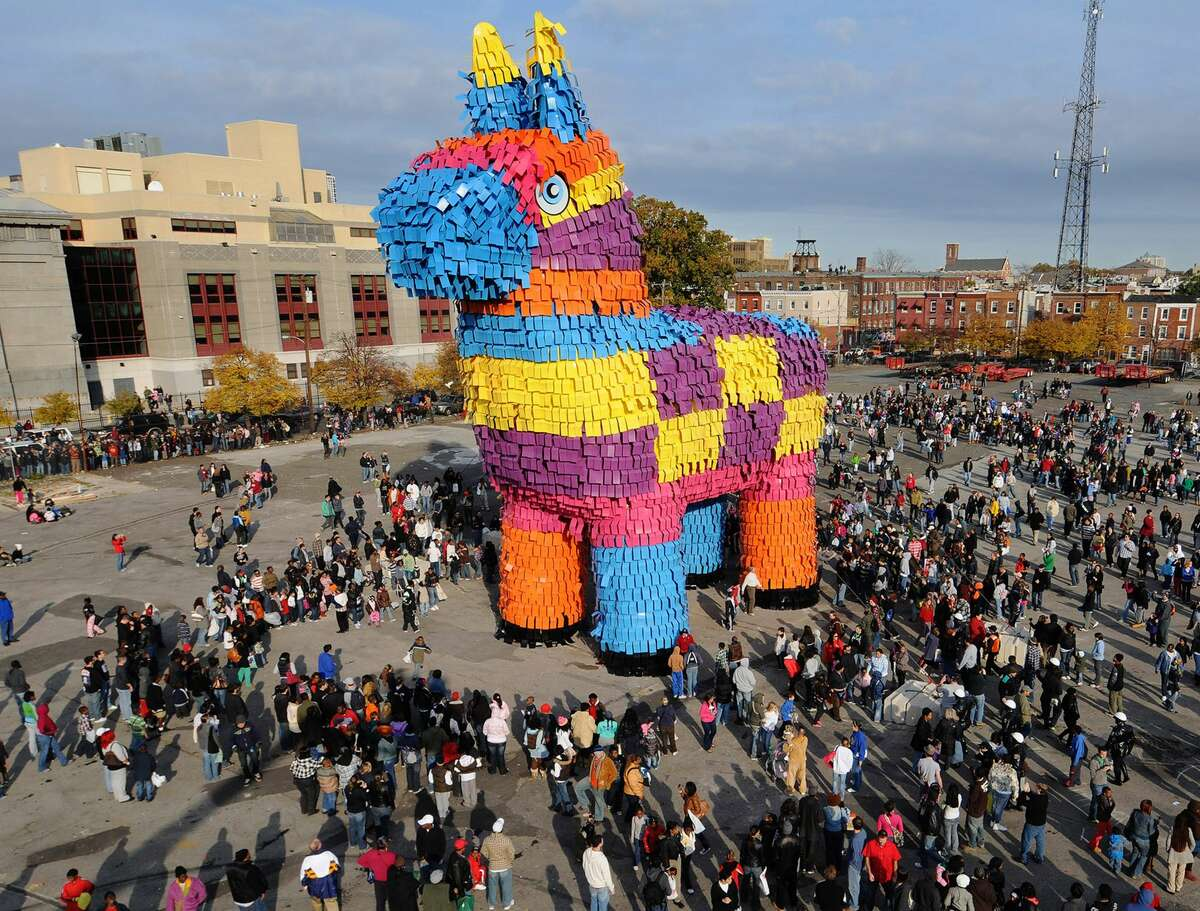 In this handout image supplied by Carnival Cruise Lines, film extras surround a huge pinata, which has broken the Guinness Record for the world's largest pinata, on November 2, 2008 in Philadelphia, Pennsylvania. The giant mock donkey measures 60 feet, 4 inches long; 23 feet, 10.5 inches wide and 61 feet, 10.25 inches tall and is filled with 8,000 pounds of candy. A wrecking ball will be used later on Sunday to smash the pinata during a public event.
