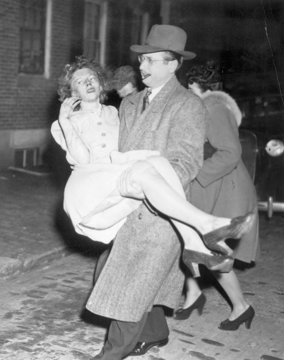 Cocoanut Grove, Boston - Nov. 28, 1942; 492 killed Photo shows a guest being carried to a waiting ambulance by one of the many civilians who helped police and firemen. The fire, one of the worst in the nation's history, occurred during the height of festivities.