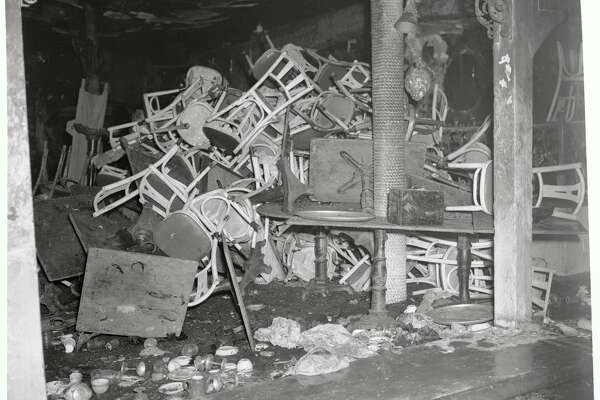 (Original Caption) Charred tables and chairs, broken wine glasses and other debris clutter a section of Boston's destroyed Cocoanut Grove Night Club. Fire swept through the popular night spot on the night of November 28, and panic reigned among the capacity crowd of 750. Toll of lives lost in the tragic accident is 432, while 214 injured crowd the city's hospitals.