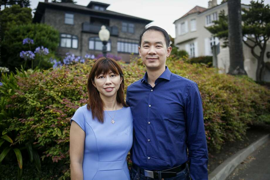 Hiuyan Tina Lam, left, and her husband Michael Cheng, right, stand for a portrait on Presidio Terrace, a street she bought in auction from the City of San Francisco, that is inside the exclusive gated community of Presidio Terrace in San Francisco on Friday, August 4, 2017. Photo: Nicole Boliaux, The Chronicle