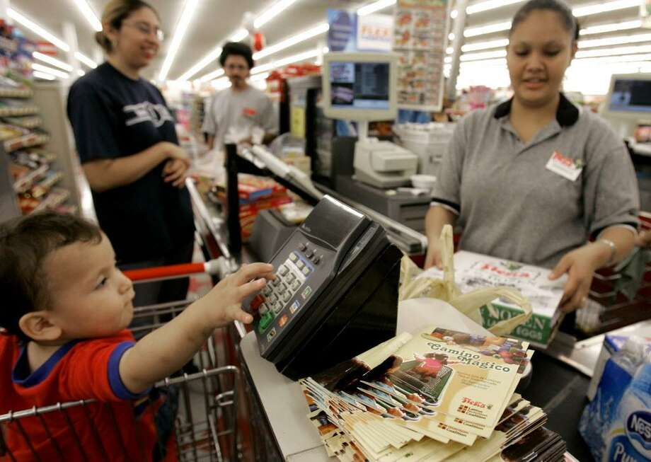 A clerk checks out groceries for a family. Photo: File Photo / AP