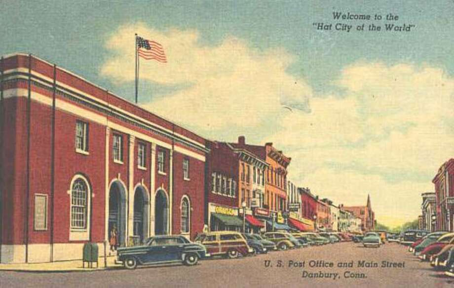 "This postcard image shows the flag of the United States of America waving over the post office on Main Street in Danbury. A message in the upper right hand corner welcomes visitors to the ""Hat City of the World."" Photo: Contributed Photo / The News-Times Contributed"
