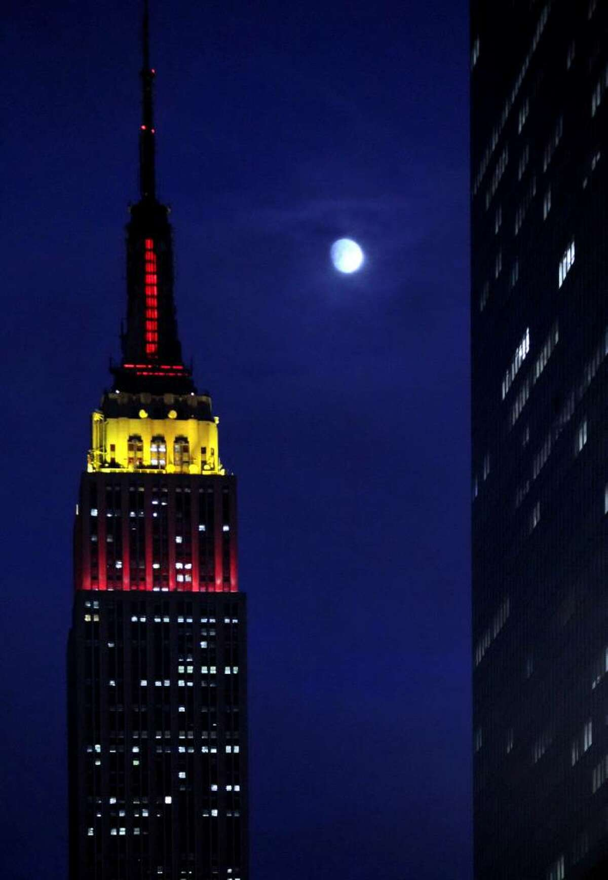 In this Sept. 30, 2009 file photo, the moon rises above New York as the Empire State Building is lit in red and yellow in honor of communist China's 60th anniversary. Catholics are criticizing the owners of the landmark skyscraper for declining to illuminate it in honor of the late Mother Teresa, who would have turned 100 on Aug. 26, 2010.