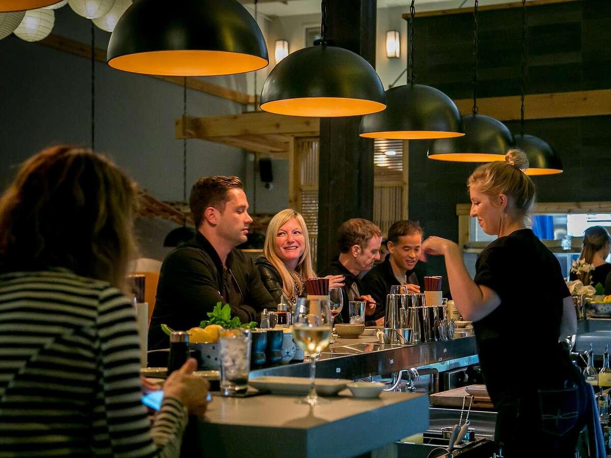 People have dinner at the bar at Mamanoko.