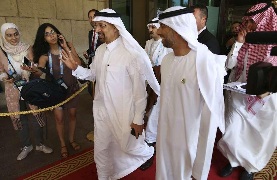 Saudi Energy Minister Khalid al-Falih (left) waves off questions as he leaves a Dubai conference. Photo: Jon Gambrell, Associated Press