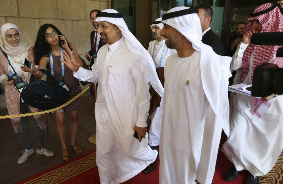 Saudi Energy Minister Khalid al-Falih (left) waves off questions as he leaves a Dubai conference. Photo: Jon Gambrell, Associated Press