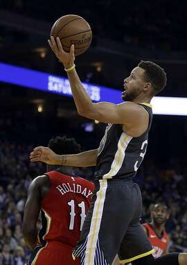Golden State Warriors guard Stephen Curry, right, shoots over New Orleans Pelicans guard Jrue Holiday (11) during the second half of an NBA basketball game Saturday, Nov. 25, 2017, in Oakland, Calif. The Warriors won, 110-95. (AP Photo/Ben Margot)