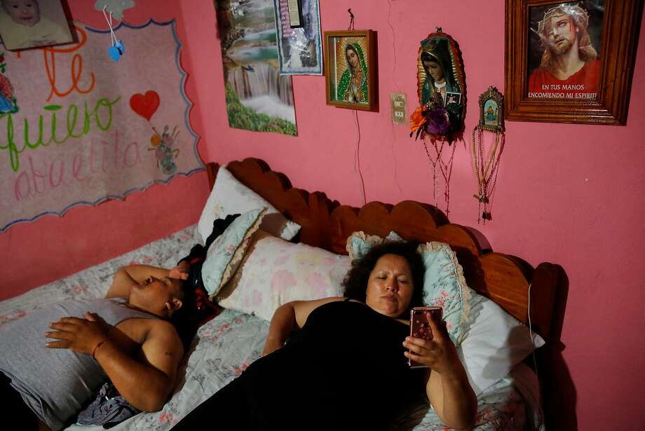 Maria Mendoza-Sanchez video chats with her daughters as her husband Eusebio Sanchez sleeps next to her before bed in their room which is normally Maria's mother's room in her mother's home Sept. 28, 2017 in Santa Monica, Hidalgo, Mexico. Photo: Leah Millis, The Chronicle